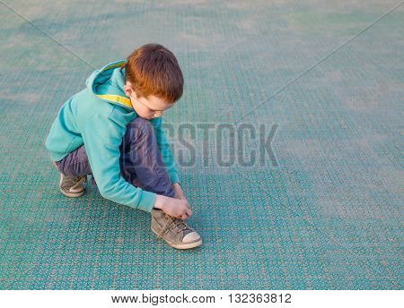 child tying shoelaces. boy trying to tie his sneakers on the sports ground. copy space for your text