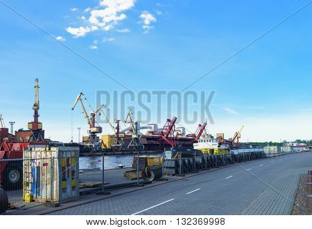 Dry Cargo Vessel And Loading Cranes At Marina In Ventspils