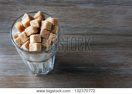 Highball glass with brown and white lump sugar on wooden table