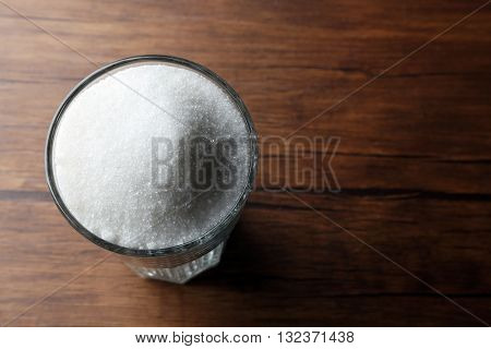 Highball glass with granulated sugar on wooden table