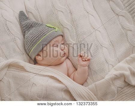 Sleppy little baby in the cap under the blanket
