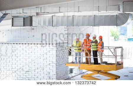 High. A group of cheerful and smiling builders standing together at an elevator and poking somewhere