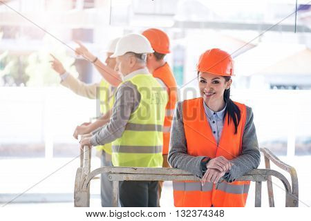 Just smile. Smiling and pretty businesswoman standing with a group of positive and content businessmen standing together and pocking in a background poster