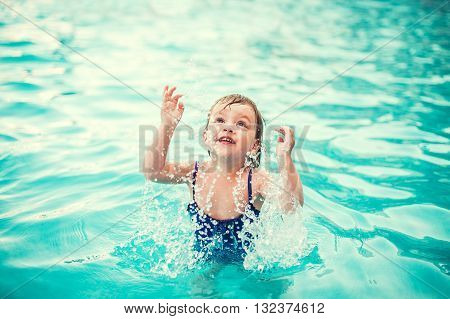 Little happy girl in swimming pool. Kid splashing on pool
