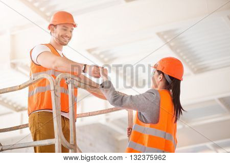 Gentleman. Generous man in a hardhat helping a cheerful woman to go up higher