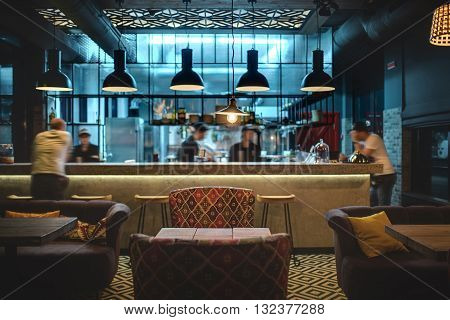 Half-lighted hall in a loft style in a mexican restaurant with open kitchen on the background. In front of the kitchen there are wooden tables with multi-colored chairs and sofas. On the sofas there are color pillows. In the kitchen there is a rack