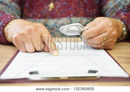 aged woman reading document with magnifying glass