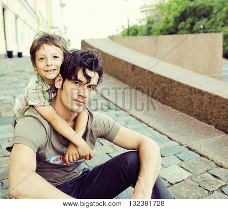little son with father in city hagging and smiling, close up