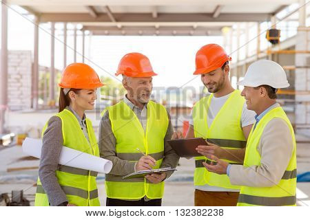 Meeting. A smiling and positive group of architectures standing together and specking about construction project with construction works on a background