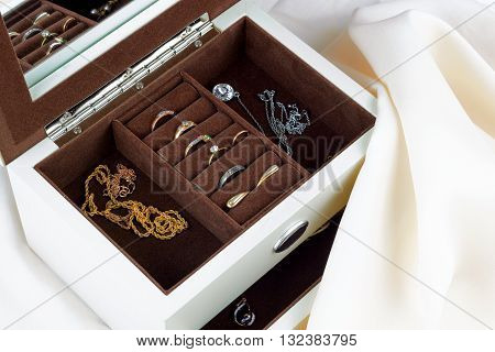 jewelry box with jewelry on silk textile background