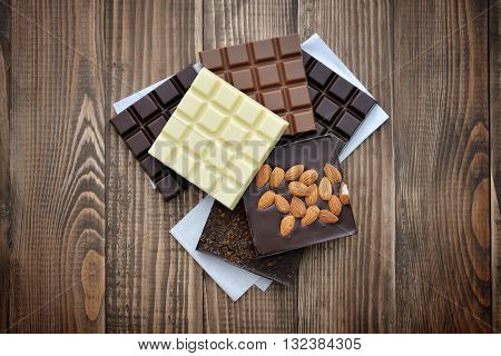 Chocolate bar from different kind of chocolate (milk black white) on wooden background