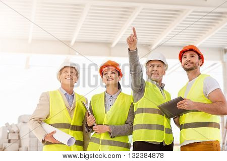 Our potentialities.  Confident and smiling engineer standing and poking somewhere for his delighted colleagues while showing and discussing new construction project