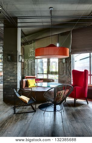 Room in a mexican restaurant in a loft style. There is a glass rounded table with black chairs, a crimson armchair and a brown sofa. Over them there is a red lampshade. Multi-colored pillows lies on the sofa and the chairs.