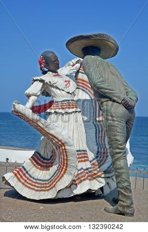 PUERTO VALLARTA MEXICO MAY 07 2016: Bronze statue to Xiutla Folkloric Dancers by local sculptor Jim Demetro, unveiled in November 2006, with the Hotel Zone and Marina Vallarta