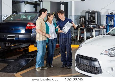 Mechanic Explaining Hubcap To Couple