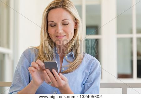 Portrait of blond mature woman using mobile phone. Smiling happy woman checking emails on smartphone. Portrait of a happy woman texting a phone message.