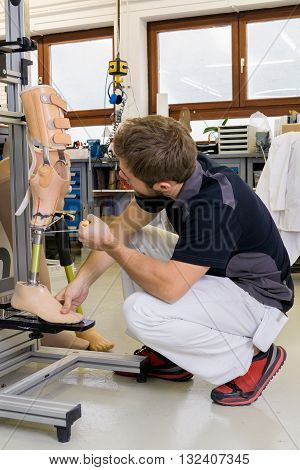 Young male technician using tool to adjust knee section on prosthetic leg assembly in laboratory for research and development