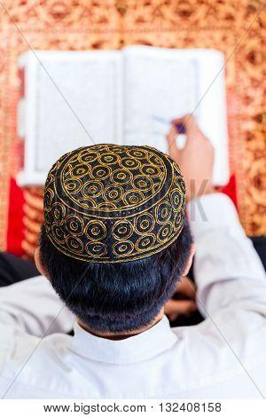 Asian Muslim man reading Koran or Quran on praying carpet wearing traditional dress