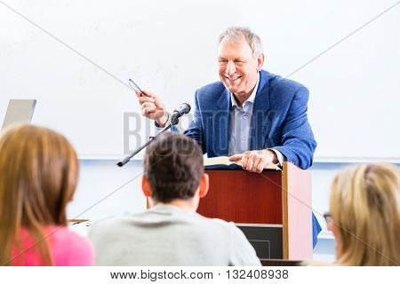 College professor giving lecture for students standing at desk
