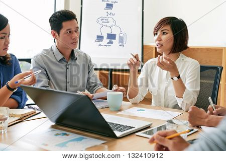 Young Asian business woman telling her ideas at meeting