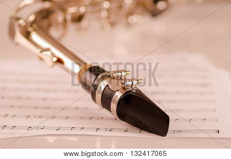 Closeup mouthpiece of saxophone lying on musical notes paper.