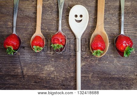 Strawberries on vintage spoons and wooden spoon with smiley face over old rustic wooden table top. Bright positive background with smileys. Summer concept for summer season. Top view.