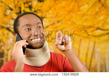 Injured young positive black hispanic male wearing neck brace and talking on phone smiling, yellow abstract background.