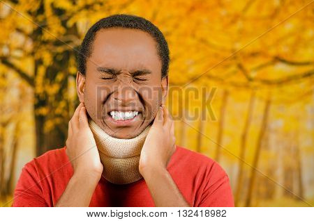 Injured young positive black hispanic male wearing neck brace, holding hands in pain around support making faces of agony, yellow abstract background.