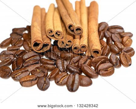 Cinnamon sticks laying on coffee beans heap against white background front view