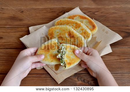 Child holds a pie in his hands. Fried pies with cottage cheese, green onion and dill. Homemade fresh patties on paper on a wooden table. Quick recipe. Delicious snacks for kids