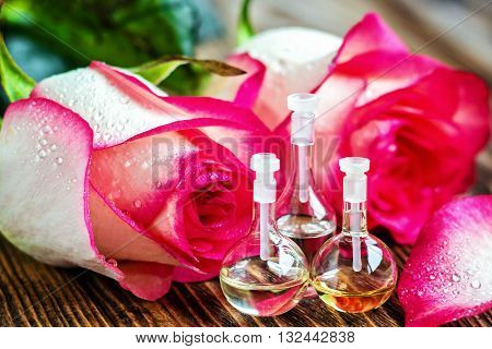 Essential oil in glass bottle with rose flowers and petals on wooden background. Beauty treatment. Spa concept. Selective focus.