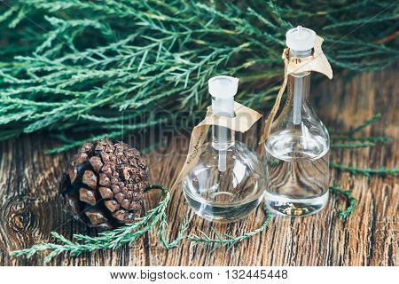 glass bottles of essential oil with pine cones on wooden background