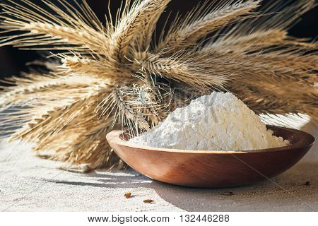 flour with wheat ears in a wooden bowl on a burlap background