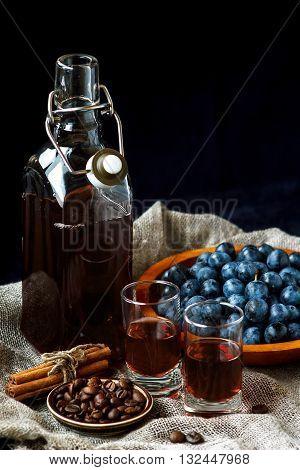 Sloe gin. Glass of blackthorn homemade light sweet reddish-brown liquid. Sloe-flavored liqueur or wine decorated with fresh juicy ripe prunus spinosa berries on burlap background. Selective focus