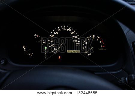 Black dashboard, speedometer, odometer, fuel gauge in the tank, tachometer, illuminated instrument panel, black interior
