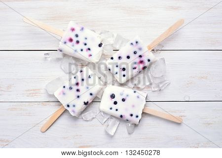 Homemade frozen ice cream popsicles from yogurt and blueberry on wooden bckground top view