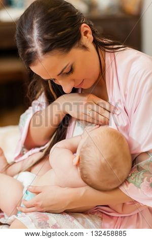 Young mum nurses the child on  on the house bed. Breastfeeding.