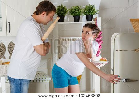 Hungry young pregnant woman and her husband standing near refrigerator in the kitchen.