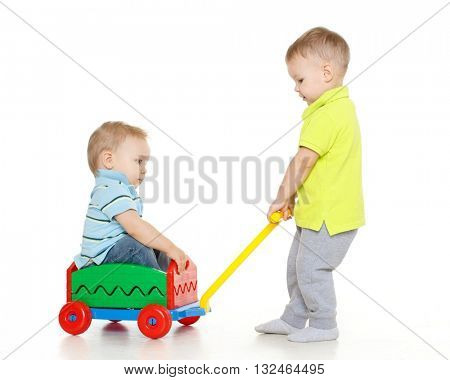Children are playing with toy handcart on a white background. One little boy sits in handcart, another child pulls him. Merry riding.