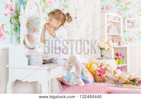 Pretty little girl playing with cosmetics near dressing table in the room. 2 year old.