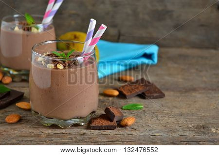 chocolate smoothie with banana and almonds on a wooden background with space for text