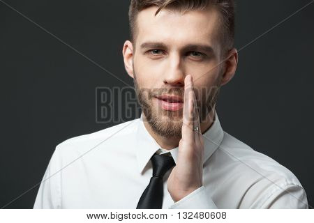 Young Businessman Whispering Trade Secrets On Dark Gray Background.