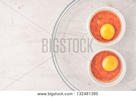 Raw eggs with tomatoes in the ramekins on the white wooden table top view