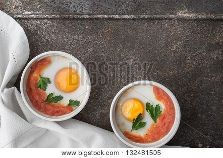 Eggs baked with tomatoes and parsley in the ramekins on the metal background top view
