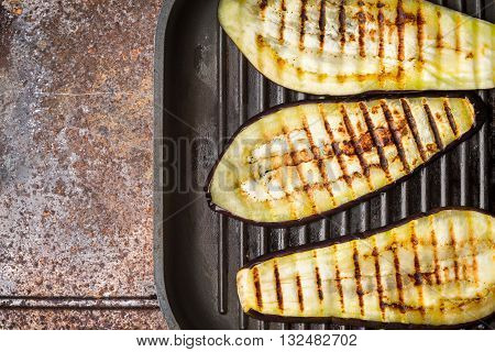 Grilled eggplants on the metal background top view