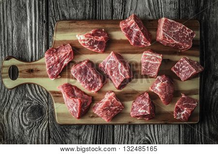 Raw angus beef slices on the old wooden table horizontal