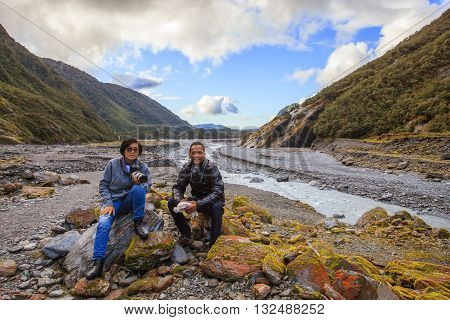 couples of asian travelers taking a photograph in franz josef glacier important traveling destination in south island new zealand