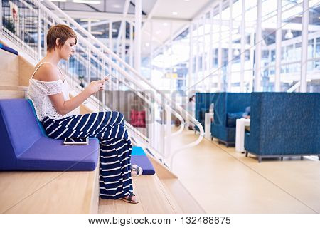 Young caucasian female creative with short brwon hair sitting on a colourful cushion in a co working space while texting about business on her smartphone, with her tablet by her side.