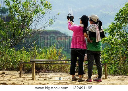 Kota Kinabalu,Sabah-May 22,2016:A group of teenager taking picture selfie with handphone on the top of Bukit Padang,Kota Kinabalu,Sabah.