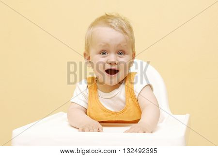 Portrait Of Happy Young Baby Boy In High Chair ready to eat